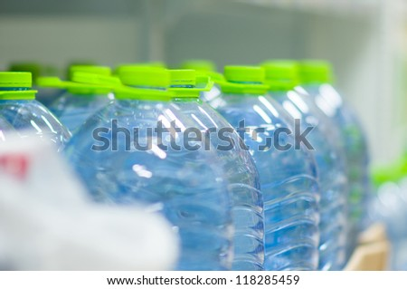Bottles of fresh water with green cups in supermarket