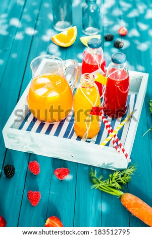 Bottles of freshly squeezed homemade citrus and berry juice with a jug of iced carrot and orange juice blend served on a wooden tray on a colorful turquoise picnic table outdoors - stock photo
