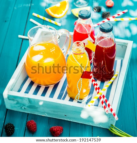 Bottles of freshly squeezed orange and berry juice standing on a wooden tray on a colorful turquoise blue picnic table in dappled summer sun - stock photo
