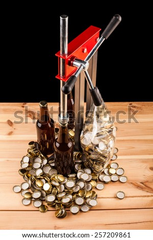 bottles  of homemade beer  and bottle capping machine on table - stock photo