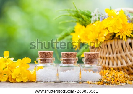 Bottles of homeopathy globules and healthy herbs in wicker basket. - stock photo