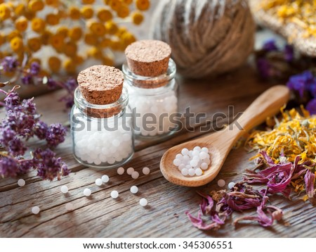 Bottles of homeopathy globules, wooden spoon and dry healthy herbs. Selective focus. - stock photo