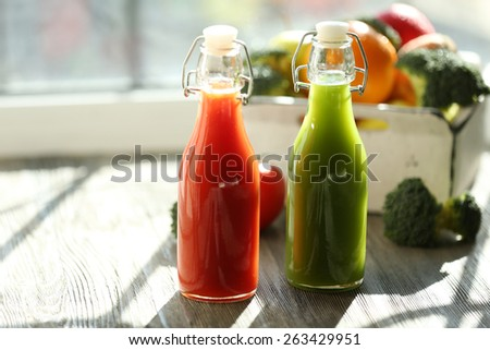 Bottles of juice with fruits and vegetables  in crate on windowsill - stock photo