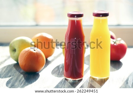 Bottles of juice with fruits and vegetables on windowsill - stock photo