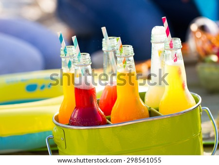 Bottles of lemonade , standing in a colorful green bucket on the beach in the summer sun. Picnic Time! - stock photo