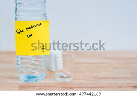 "Bottles of medicine capsules, pills in small glass. And water bottle with message ""take medicine too"" on wooden floor. With copy space."