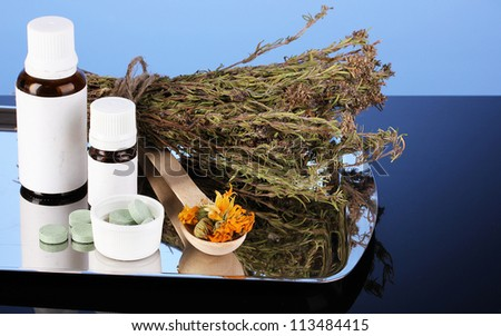 bottles of medicines and herbs on blue background. concept of homeopathy - stock photo