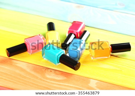 Bottles of nail polish on a colorful wooden table - stock photo