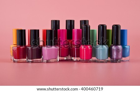 bottles of nail polish on a pink background close up