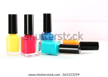 Bottles of nail polish on a wooden table - stock photo