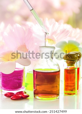 Bottles of natural aroma oil, essentials and fragrances aligned with flowers background - stock photo