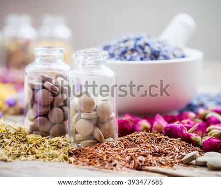 Bottles of natural tablets, healing herbs and mortar with dry lavender flowers, herbal medicine. - stock photo