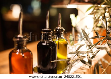 bottles of oil with tips standing on wooden table with oil tree - stock photo