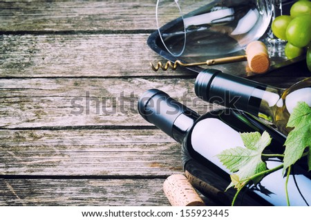 Bottles of red and white wine on wooden table - stock photo