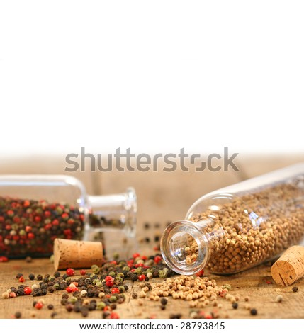 Bottles of spices on rustic wood table - stock photo