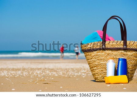 Bottles of sun screen in a basket. A happy older couple in the blurred background - stock photo