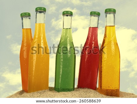 Bottles of tasty drink on sand isolated on white