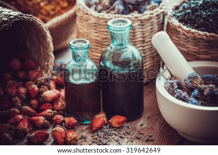 Bottles of tincture, basket with rose buds, and dried forget me not flowers in mortar. Herbal medicine. Selective focus. - stock photo