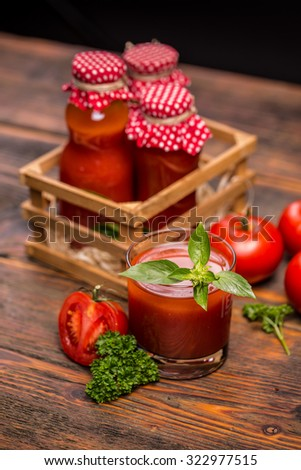 Bottles of tomato juice and ripe tomatoes - stock photo
