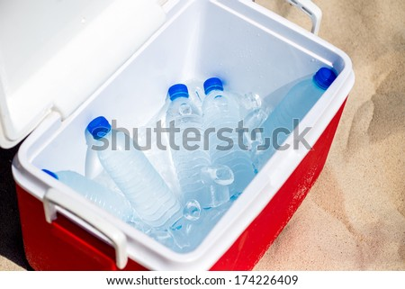 Bottles of water in the ice box on the beach - stock photo