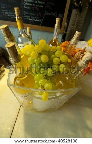 Bottles of white wines with a grape - stock photo