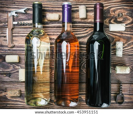 bottles of wine and various accessories on wooden table - stock photo