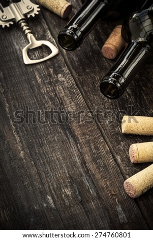 Bottles of wine, corks and corkscrew on wooden background. Toned image - stock photo