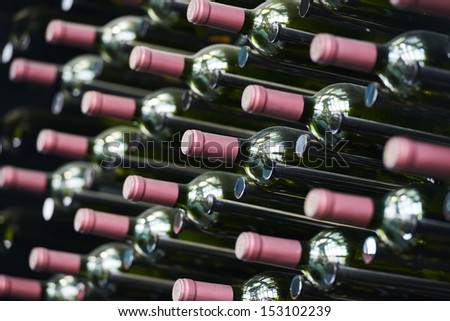 Bottles of wine in row stacked in cellar. shallow depth of view. - stock photo