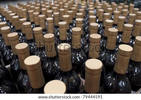 Bottles of wine in rows in liquor store - stock photo