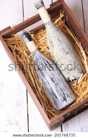 Bottles of wine in wooden box, on wooden background - stock photo