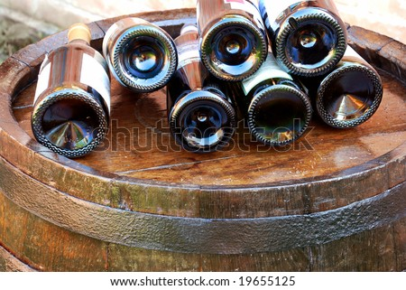 bottles of wine lying over wooden barrel - stock photo