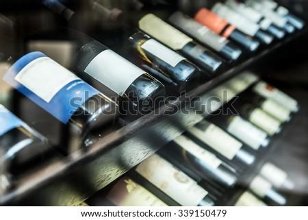 Bottles of wine on the wooden shelf. - stock photo