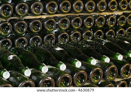 Bottles of wine stocked in a wine cellar - stock photo