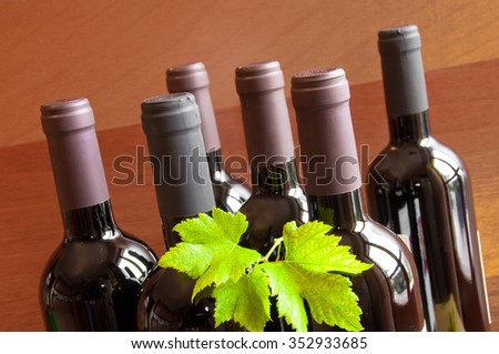 Bottles of wine with green grape leaves on wood - stock photo