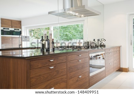 Bottles on countertop with wooden drawers in modern kitchen - stock photo