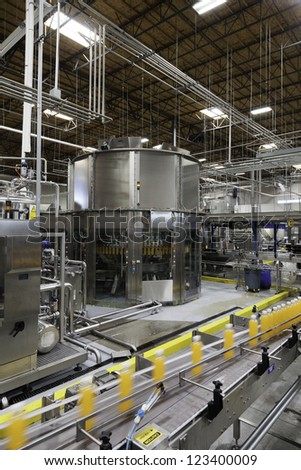 Bottles on production line at bottling plant - stock photo