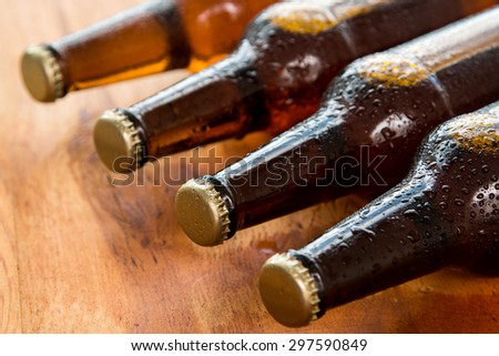 Bottles with cold beer on wooden table - stock photo