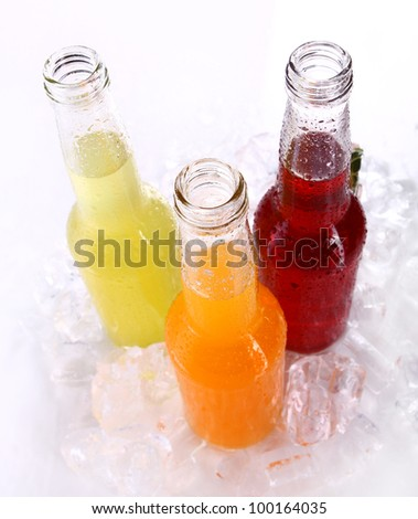 Bottles with colorful cocktail and ice over white background - stock photo