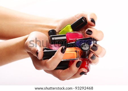 Bottles with colorful nail polish in the hands over white background - stock photo