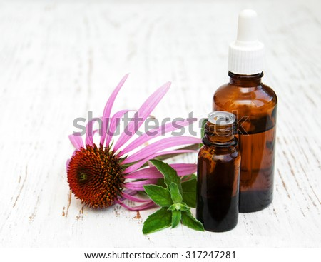 bottles with essence oil with purple echinacea on a wooden background - stock photo