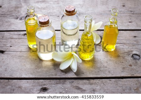 Bottles with essential aroma oil and tropical flowers plumeria  on wooden background. Selective focus. Place for text. - stock photo