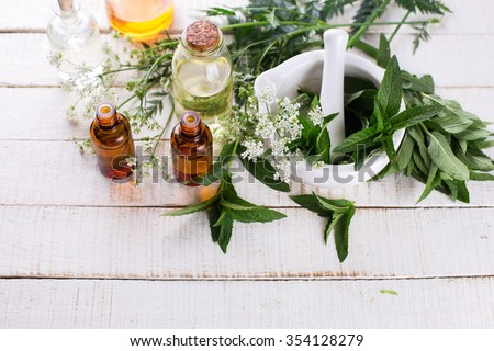 Bottles with essential aroma oil with mint  on white painted wooden background. Selective focus. Place for text. - stock photo