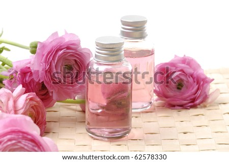 bottles with essential oil and pink dahlia flower on woven mat - stock photo