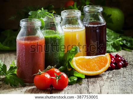 Bottles with fresh juices from fruits and vegetables on an old wooden background, selective focus - stock photo