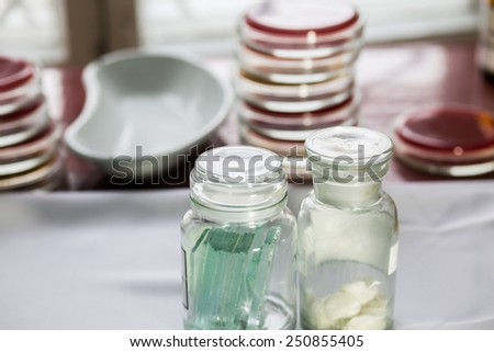 Bottles with glass pieces and swabs in a lab; Petri dishes stacked on the background. Medical tests and research. Hospital labotory glassware. - stock photo