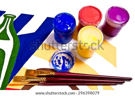 Bottles with gouache paints and different kinds of brushes for artistic paintings.Original artistic painting of still life on the background. - stock photo