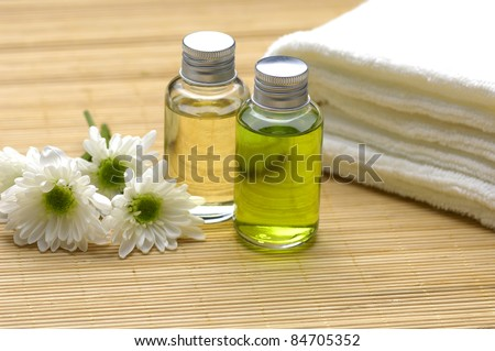 bottles with massage oils and towel with flower on bamboo stick straw mat - stock photo