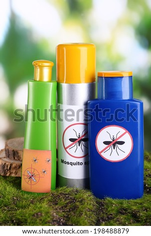 Bottles with mosquito repellent cream on nature background - stock photo