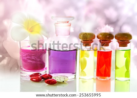 Bottles with natural aroma oil on flowers background  - stock photo