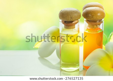 bottles with natural aroma oil on light green nature background - stock photo